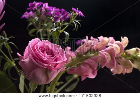 Pink rose in a small bouquet of flowers.