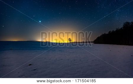 Milky Way And Starry Sky Over Winter Landscape And Distant Village