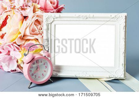 Empty vintage photo frame and pink alarm clock with roses flower on gray background Save clipping path.
