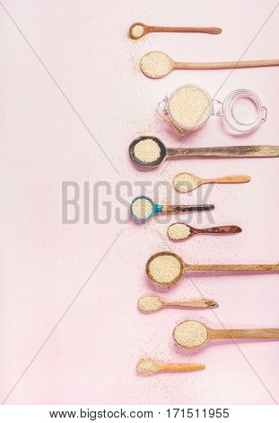 Quinoa seeds in different spoons and glass jar over light pink background, top view, copy space. Superfood, healthy eating, dieting, clean eating, detox or vegetarian food concept