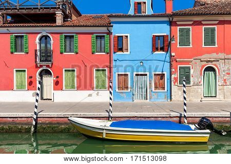 Boat on small canal in front of old colorful houses on Burano island in Italy.
