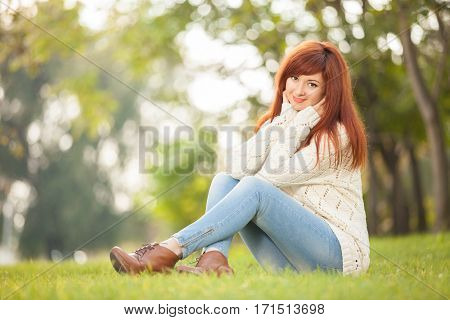Young woman walking in the park. Beauty nature scene with colorful background at spring season. Outdoor lifestyle. Happy smiling woman relax on green grass