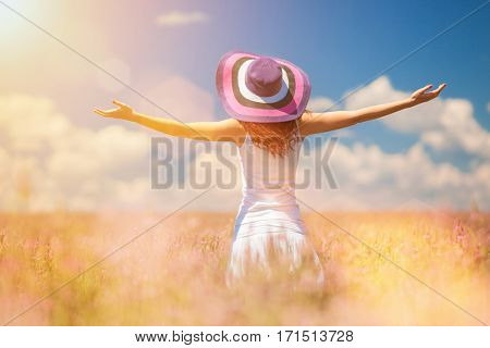 Happy woman enjoying the life in the field with flowers. Nature beauty, blue cloudy sky and colorful field with flowers. Outdoor lifestyle. Freedom concept. Woman in summer field