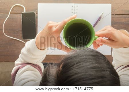 Working creative table and hot green tea drinking stock photo