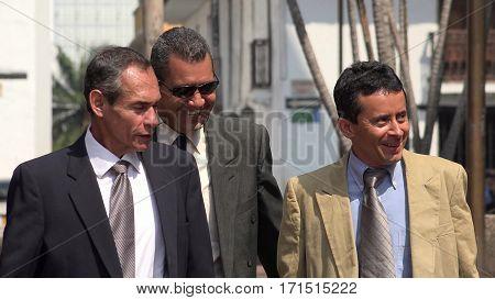Businessmen Walking On Sidewalk and Wearing Business Suits