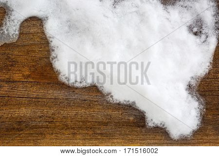 Closeup photo of snowflake, ice crystals on brown wooden background with copyspace