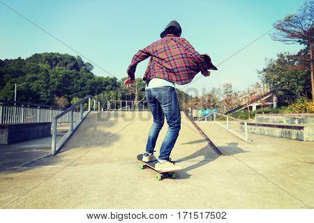 young skateboarder riding skateboard at skate park