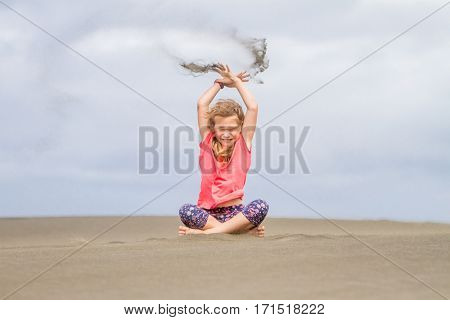 young child girl throwing sand up on empty beach