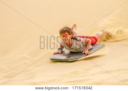 happy child boy sliding a board on sand dunes, family fun