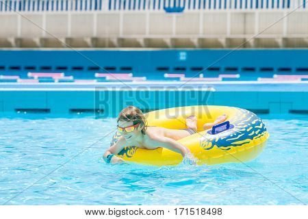 portrait of young boy having fun in water pool