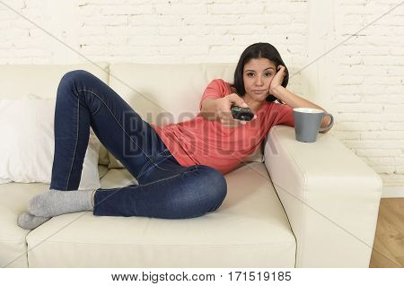young beautiful hispanic woman sitting at home sofa couch in living room watching television looking tired and bored disappointed holding remote control switching channels