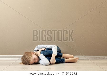 Upset girl lying on the floor at home