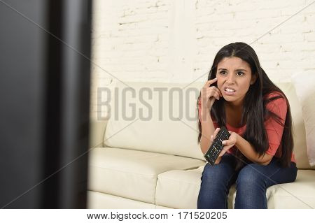 young beautiful latina woman sitting at home sofa couch in living room watching television news looking tired and bored disappointed holding remote control in negative emotion