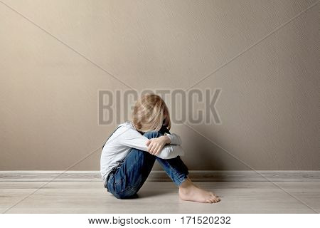 Upset girl sitting on the floor at home