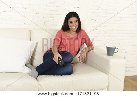 young beautiful Spanish woman in jeans home alone watching television smiling sitting at sofa couch on living room happy and excited enjoying TV romantic comedy movie relaxed