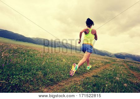 young fitness woman trail runner running on grassland