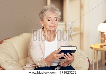 Depressed elderly woman with book sitting on lounge at home