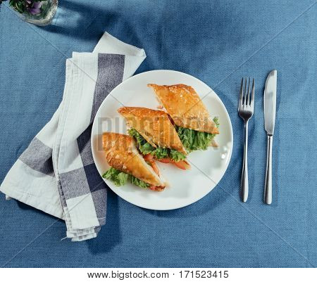 Healthy sandwich cut into pieces to show tasty ingredients salami, tomatoes, lettuce.