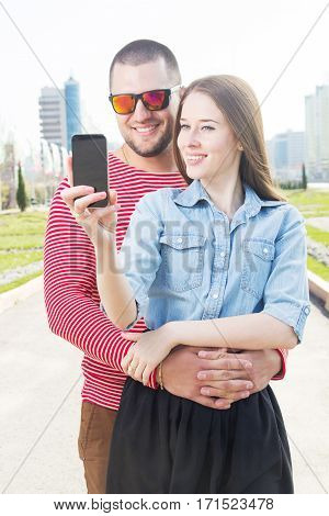Beautiful man and woman walking on the street and making selfie by smart phone.