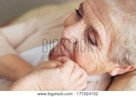 Depressed elderly woman at home, closeup