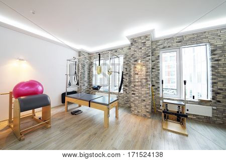 Empty hall with modern equipment for pilates training - fitball and trainers