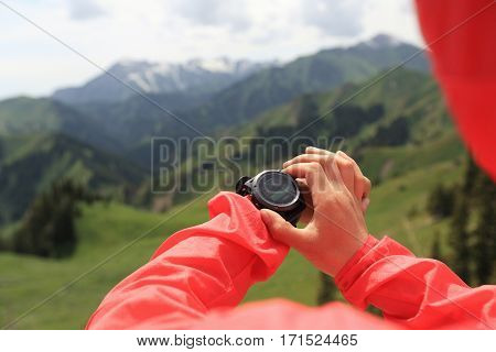 young woman hiker checking the altimeter on mountain
