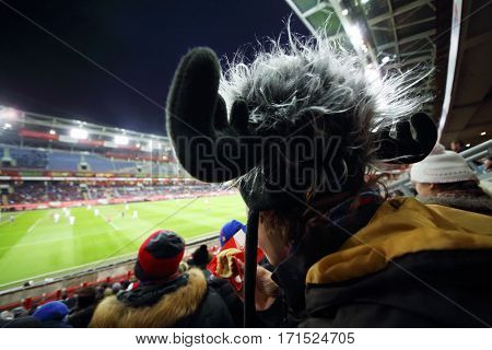 Eating boy in hat with horns and stands during football match at evening stadium