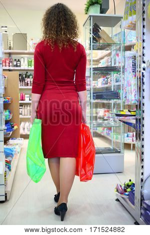 Woman in red with two bags in supermarket Goods for Home, back view