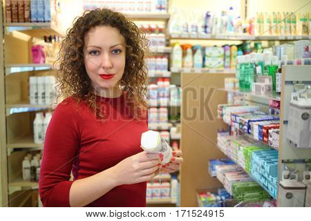 Pretty woman in red holds cotton pads in Goods for Home shop