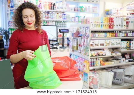 Pretty smiling woman in red packs purchase in Goods for Home shop