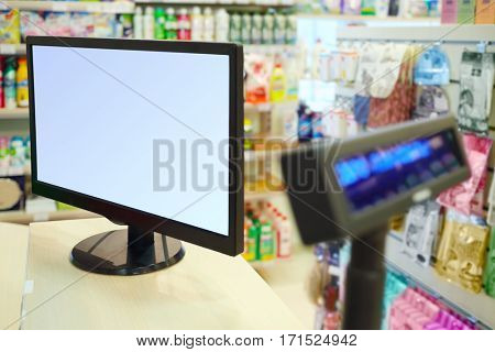 Cash register display in store, many goods for home are on shelves out of focus