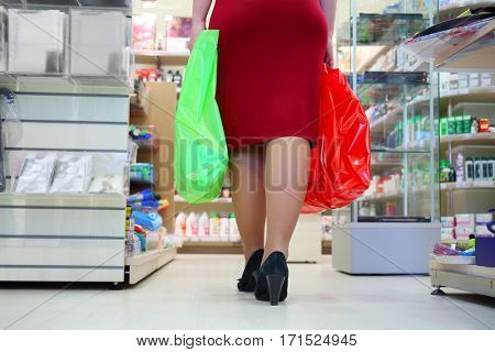 Woman in red with two bags in supermarket, back view, noface