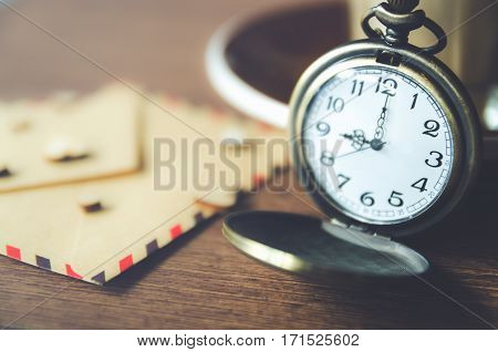 vintage pocket watch  on wood table with old paper