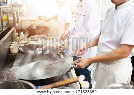 Group Of Chefs In Hotel Or Restaurant Kitchen Busy Cooking