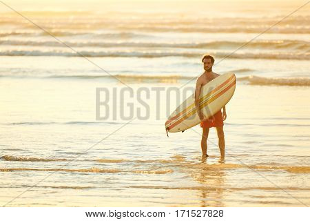 Wide shot of man holding surfboard standing in the water of the shallow surf on the beach early in the morning for sunrise to catch the waves first.