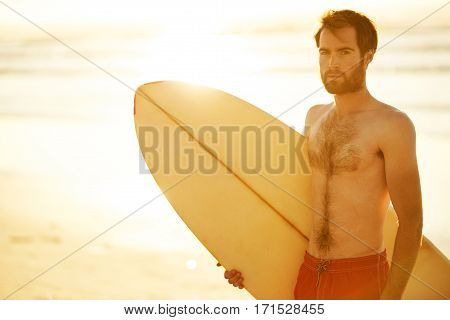 Caucasian male surfer holding a retro surfboard under his arm while looking sideways off camera, with copy space over the ocean waves in the background behind him.