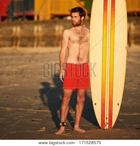 Full body colourful image of young caucasian male surfer wearing a bright red pair of shorts while standing on the beach with his surfboard standing upright next to him.