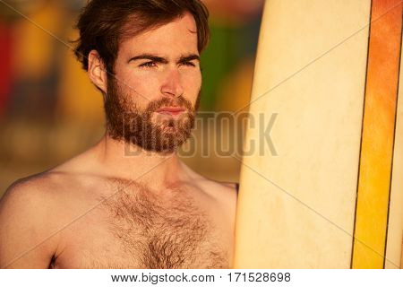 Close up horizontal image of bearded caucasian surfer standing next to his surfboard with a colourful background.