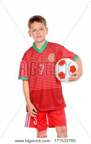 Nine year old boy football player in his uniform with a soccer ball. Isolated over white background.