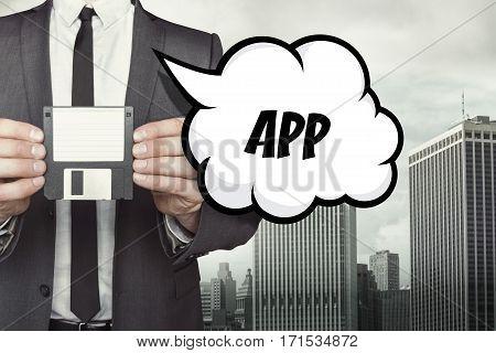 App text on speech bubble with businessman holding diskette