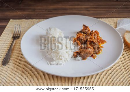Scene with snow white ceramic dish of rice and roast meat, stew, meats with vegetables on a bamboo napkin on a wooden table from the old boards. Slices of white bread on the white paper napkins