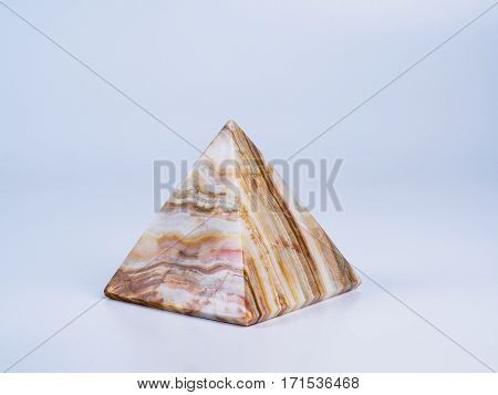 Picture of the onyx pyramid on white background. Side view. Onyx texture pattern.