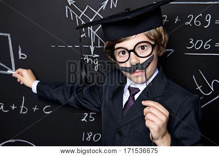 Smart schoolboy in black suit and glasses over school blackboard. Educational concept.