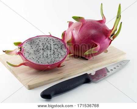 dragon fruit on wooden chopping board and kitchen knife on white background, tropical fruit sweet taste and succulent