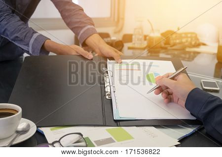 Business people negotiating a contract they are pointing on a document and discussing together