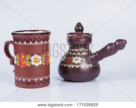 Picture of the brown-coloured coffee cup near dark brown jezve isolated on white background. Tea cup and jezve decorated with design on white background. Handmade earthenware. Side view.