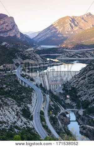 View of hydro-electric power station and a highway. Dam at Sege river, Oliana, Spain, Europe. Mountain peaks landscape.