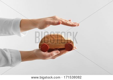 Car protection concept. Female hand holding wooden toy car on white background