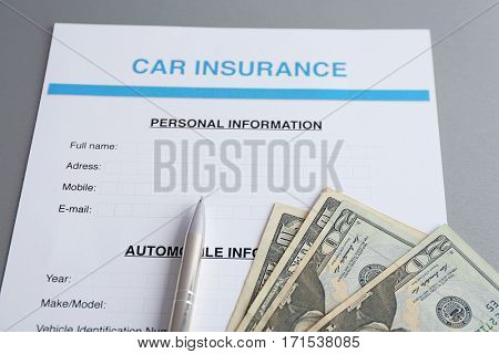 Car insurance form and money on table