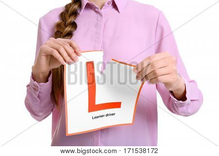 Young woman tearing learner driver sign on white background, closeup